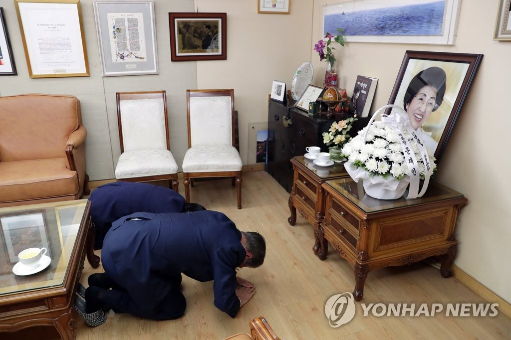 President Moon Jae-in (R) and first lady Kim Jung-sook bow in front of a photo of late former first lady Lee Hee-ho at her home in Donggyo-dong, Seoul, on June 16, 2019, in this photo provided by Cheong Wa Dae. (PHOTO NOT FOR SALE) (Yonhap)