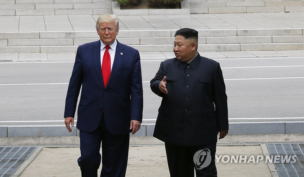 U.S. President Donald Trump (L) and North Korean leader Kim Jong-un walk toward the southern side of the Military Demarcation Line that divides the two Koreas at the border truce village of Panmunjom, in what has become their third summit, on June 30, 2019. (Yonhap)