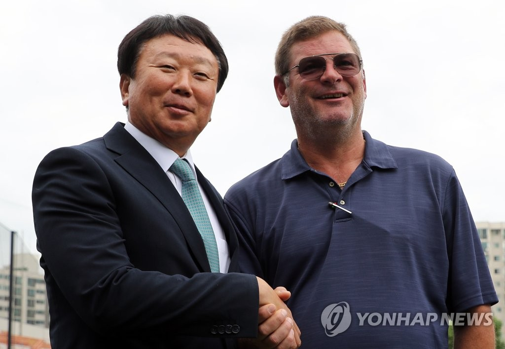 Sun Dong-yol (L), former South Korean national baseball team manager, shakes hands with New York Yankees' Pacific Rim scouting coordinator Steve Wilson during a press conference on July 11, 2019, at Mokdong Stadium in Seoul, where Sun announced he will join the Yankees in spring training in 2020. (Yonhap)