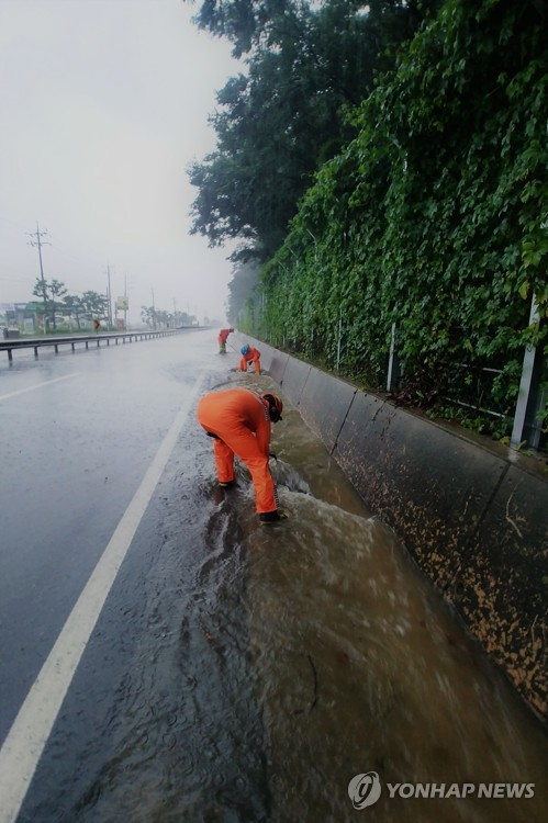 Firefighters work to restore inundated road