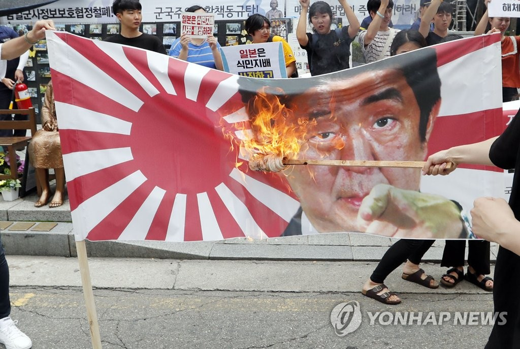 Student activists burn a banner showing Japanese Prime Minister Shinzo Abe and the Rising Sun flag in protest of the trade row in front of the old Japanese Embassy building in central Seoul on July 29, 2019. (Yonhap)