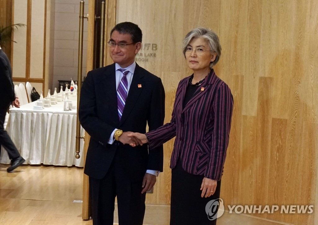 Foreign Minister Kang Kyung-wha (R) shakes hands with her Japanese counterpart, Taro Kono, before their talks in Beijing on Aug. 21, 2019. (Pool photo) (Yonhap)