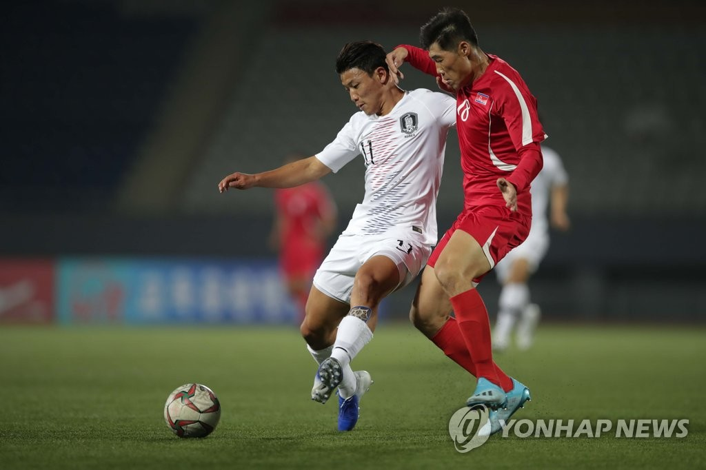 In this photo provided by the Korea Football Association, Hwang Hee-chan of South Korea (L) battles Ri Yong-chol of North Korea for the ball during the teams' World Cup qualifying match at Kim Il-sung Stadium in Pyongyang on Oct. 15, 2019. (PHOTO NOT FOR SALE) (Yonhap)
