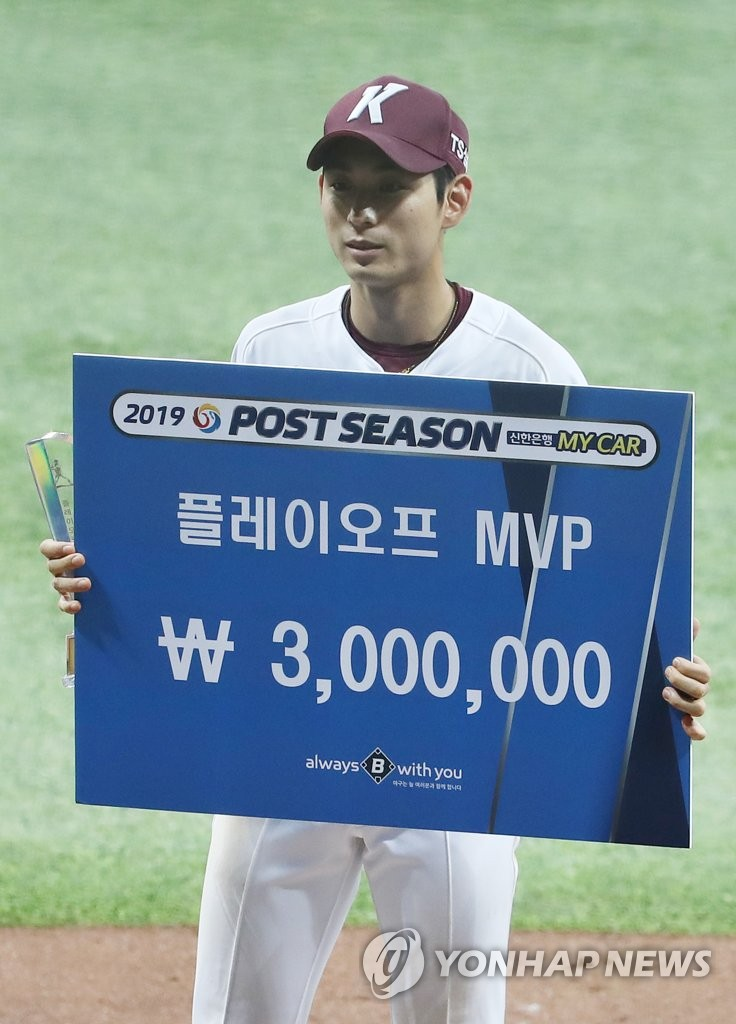 Lee Jung-hoo of the Kiwoom Heroes holds up the trophy and the oversize check after winning the MVP award for the second round Korea Baseball Organization playoff series, following the Heroes' 10-1 win over the SK Wyverns at Gocheok Sky Dome in Seoul on Oct. 17, 2019. (Yonhap)