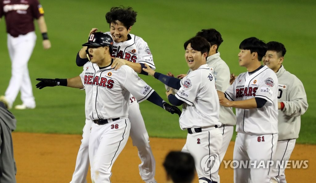 Oh Jae-il of the Doosan Bears (L) is congratulated by his teammates after hitting a walk-off single against the Kiwoom Heroes in the bottom of the ninth inning of Game 1 of the Korean Series at Jamsil Stadium in Seoul on Oct. 22, 2019. (Yonhap)