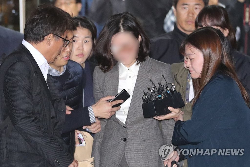 Chung Kyung-sim (C), wife of ex-Justice Minister Cho Kuk, is surrounded by reporters on Oct. 23, 2019, as she leaves a Seoul court after attending a hearing to review an arrest warrant. (Yonhap)