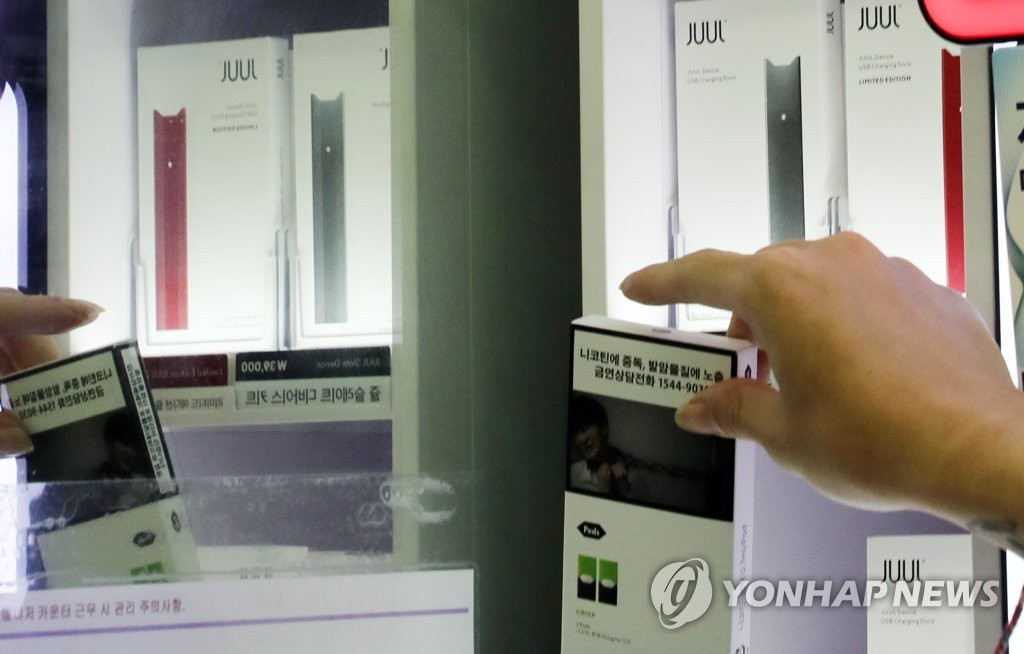 An employee of GS25 clears e-cigarettes from shelves in a Seoul store on Oct. 24, 2019, after the convenience store chain decided to suspend sales of the vaping products on concerns over harmful health effects. (Yonhap)