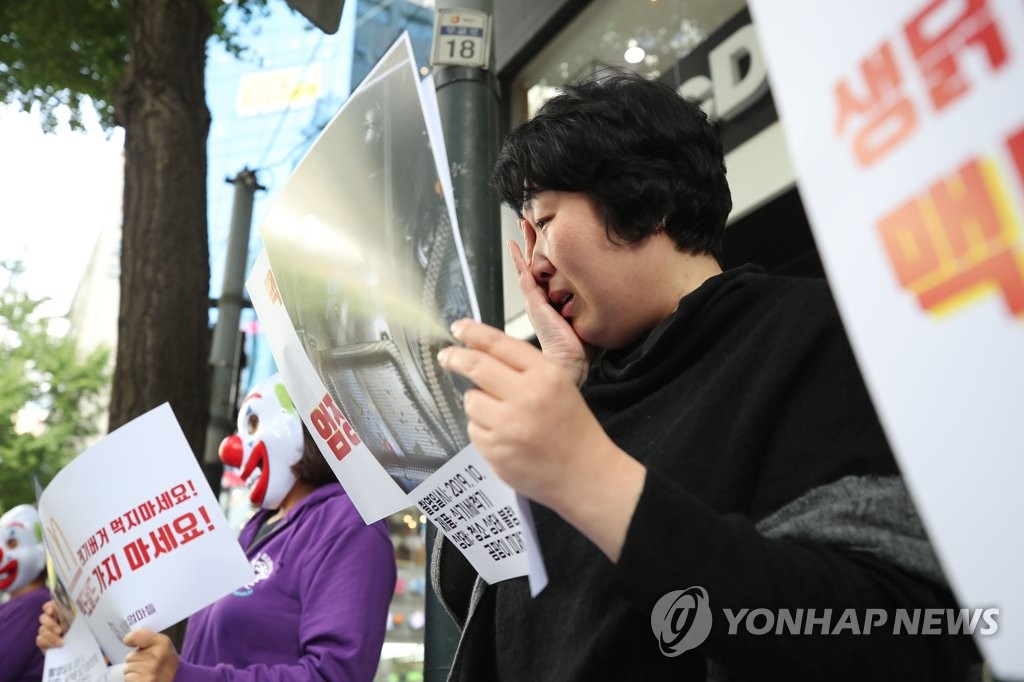"A mother of a child suffering so-called ""hamburger disease"" wipes away tears while attending a rally calling for a boycott of McDonald's in front of Seoul City Hall on Oct. 29, 2019. (Yonhap)"
