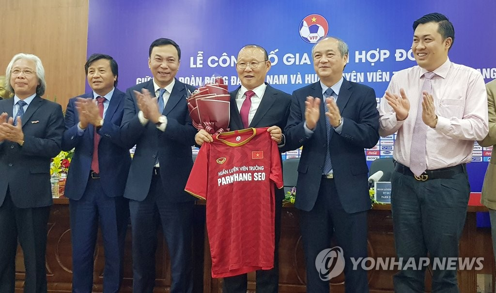 Park Hang-seo (3rd from R), South Korean head coach for the Vietnamese men's national football team, holds up a uniform bearing his name at a press conference at the Vietnam Football Federation headquarters in Hanoi on Nov. 7, 2019, announcing an extension with the team. (Yonhap)