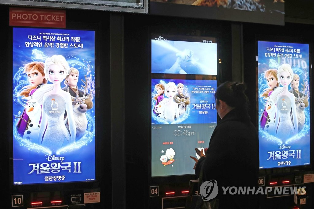 This photo shows a moviegoer in the process of buying movie tickets on a machine at a local movie theater. (Yonhap)