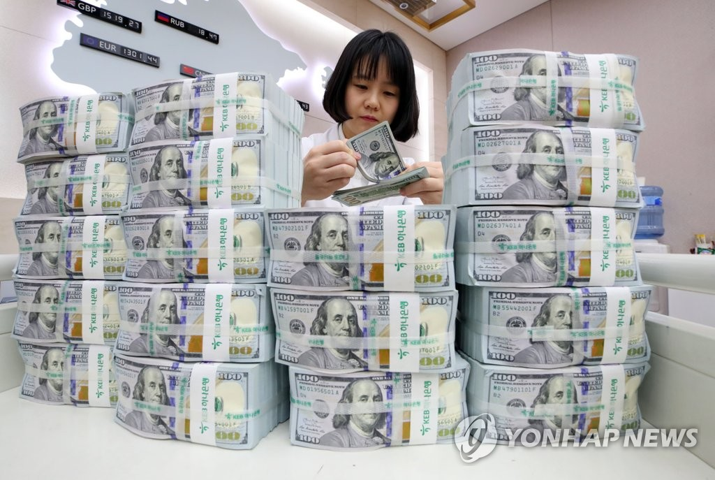 In the file photo, a bank official inspects U.S. dollar bills at a Seoul bank. (Yonhap)