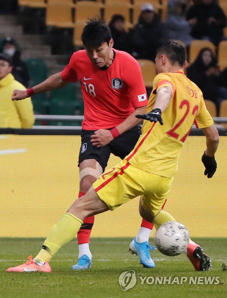 Lee Jeong-hyeop of South Korea (L) makes a pass through the legs of Yu Dabao of China during the teams' second match at the East Asian Football Federation (EAFF) E-1 Football Championship at Busan Asiad Main Stadium in Busan, 450 kilometers southeast of Seoul, on Dec. 15, 2019. (Yonhap)