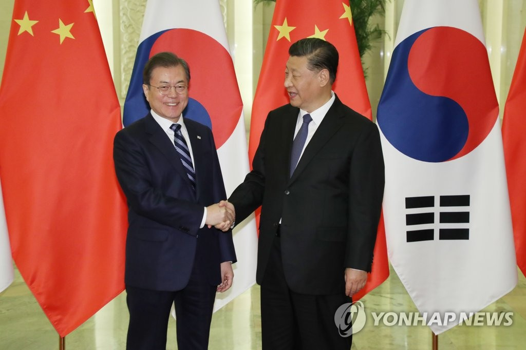 South Korean President Moon Jae-in (L) shakes hands with Chinese President Xi Jinping in their Beijing summit on Dec. 23, 2019. (Yonhap)