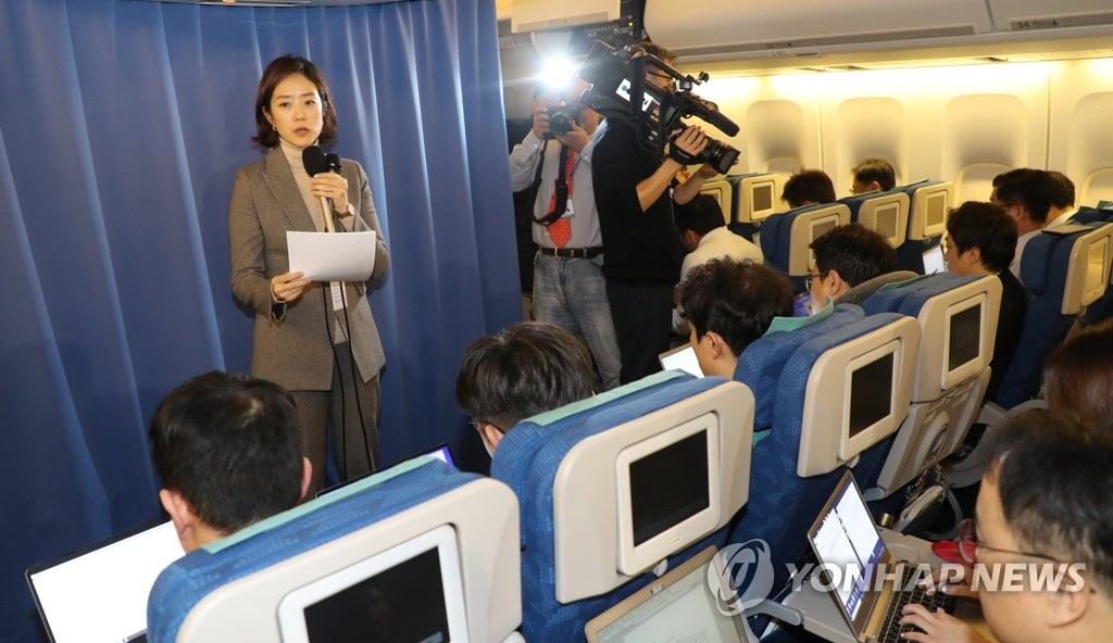 Cheong Wa Dae spokesperson Ko Min-jung (L, standing) holds an in-flight press briefing on the results of a summit between South Korean President Moon Jae-in and Chinese President Xi Jinping in Beijing on Dec. 23, 2019. (Yonhap)