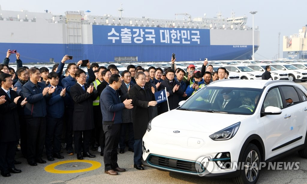 President Moon Jae-in hangs a commemorative flag on a Kia Niro crossover SUVs, the first environment-friendly vehicle exported by South Korea in 2020, at the Pyeongtaek-Dangjin port in Gyeonggi Province, on Jan. 3, 2020. (Yonhap)