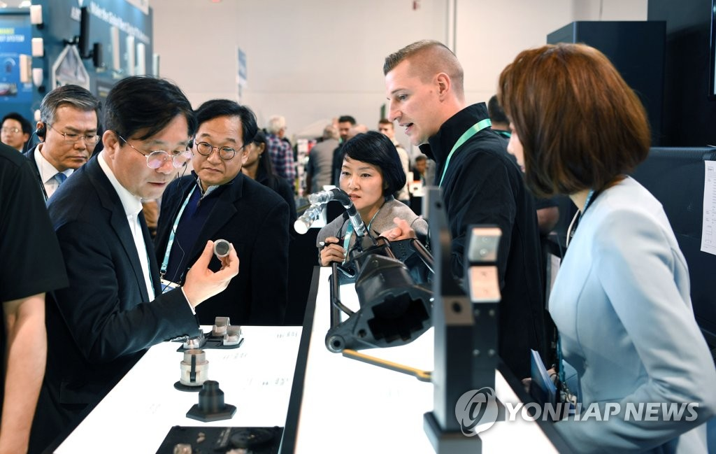 South Korea's Trade, Industry and Energy Minister Sung Yun-mo (L) looks at a robotics product at a Consumer Electronics Show (CES) exhibitor booth in Las Vegas, Nevada, in this photo provided by his ministry on Jan. 9, 2020. (PHOTO NOT FOR SALE) (Yonhap)