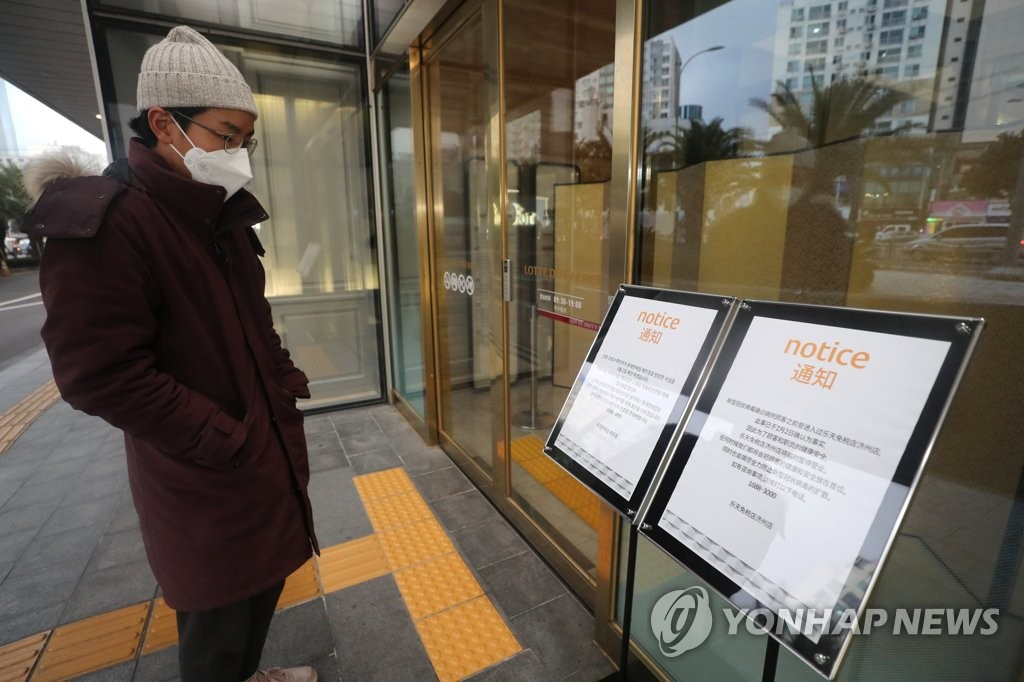 A visitor reads a notice of closure at a duty free shop on South Korea's southern resort island of Jeju on Feb. 2, 2020. The shop was forced to shut down due to a recent visit by a Chinese tourist who was subsequently diagnosed with the new strain of coronavirus that has claimed over 300 lives in China alone. (Yonhap)