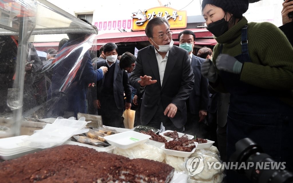 Pesident Moon Jae-in talks with a rice cake vendor at the Namdaemun Market in Seoul on Feb. 12, 2020. (Yonhap)