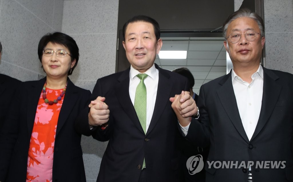Rep. Park Joo-hyun of the Party for Democracy and Peace (L), Rep. Park Joo-sun of the Bareunmirae Party (C) and Rep. You Sung-yop of the New Alternative Party pose for photos after announcing the merger of their parties at the National Assembly in Seoul on Feb. 14, 2020. (Yonhap)
