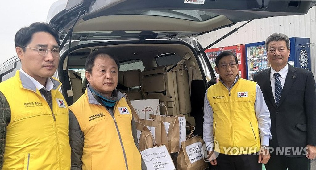 Yoon Hee-chan (2nd from R), the Korean consul general in Yokohama, and other officials pose for a photo while preparing to send food, hygiene products and other commodities to South Koreans aboard a quarantined cruise ship moored off the coast of Japan on Feb. 15, 2020. (Yonhap)