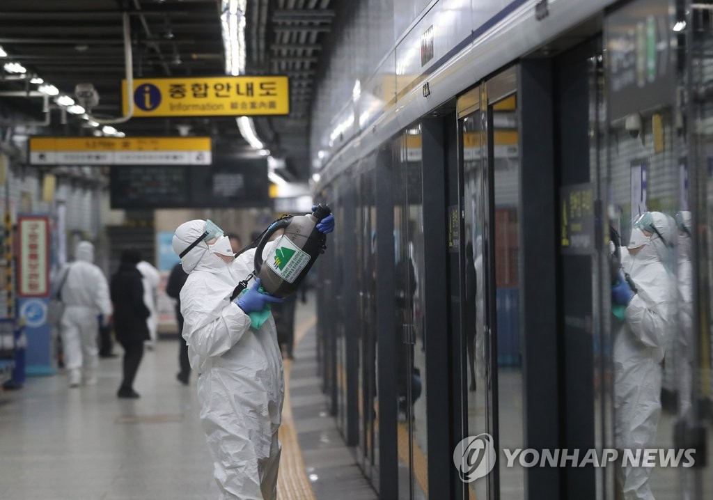 Health authorities disinfect platform screen doors at a subway station in Seoul on Feb. 21, 2020. (Yonhap)