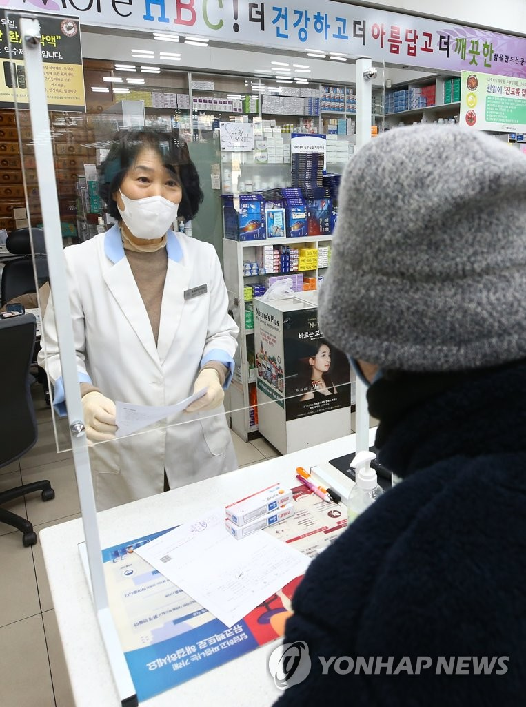 A pharmacist talks with a customer though a transparent plate at a drugstore in the southeastern city of Daegu on March 6, 2020, as part of preventive measures against the spread of the new coronavirus. (Yonhap)