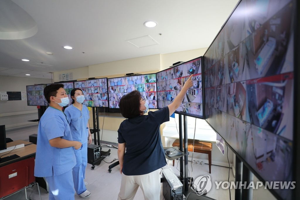 Medical workers monitor screens showing negative pressure quarantine rooms at Seoul Medical Center on March 9, 2020, where patients infected with the new coronavirus are being treated. (Yonhap)