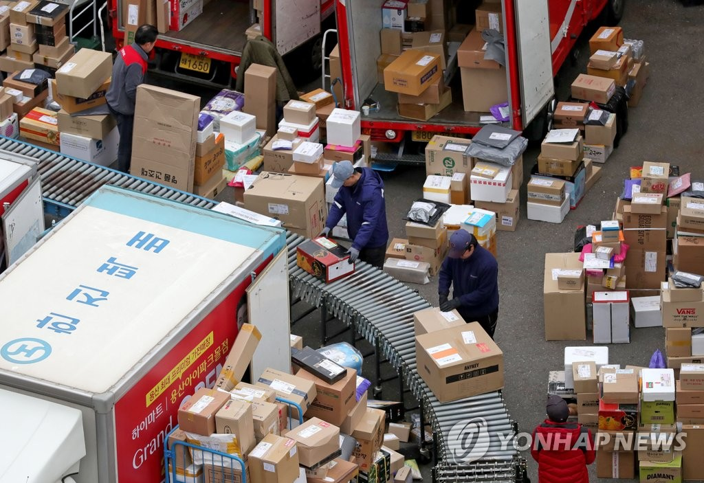 Workers handle parcels at a distribution center in Seoul on March 17, 2020, amid rising demand for delivery services. (Yonhap)