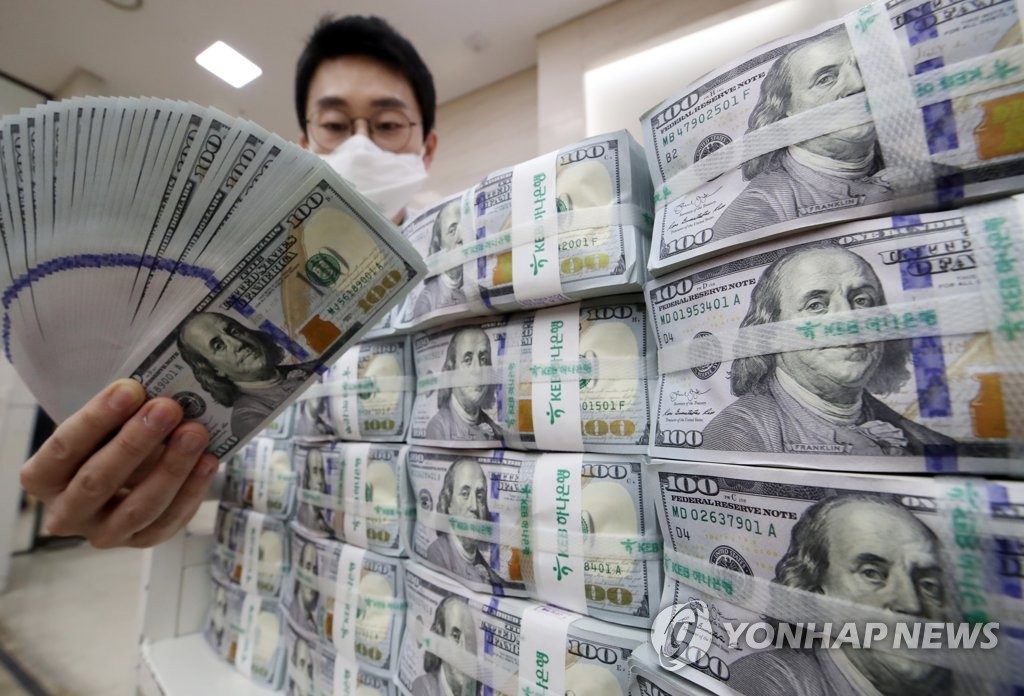 This file photo, taken on March 18, 2020, shows a Hana Bank official in Seoul inspecting U.S. banknotes before their release into the local financial market. (Yonhap)