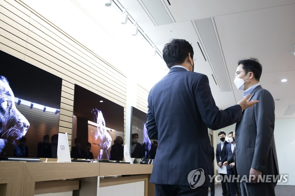 In this photo provided by Samsung Electronics Co. on March 19, 2020, Samsung Electronics Vice Chairman Lee Jae-yong (R) inspects display products from Samsung Display Co. at the company's Asan plant in South Korea. (PHOTO NOT FOR SALE) (Yonhap)
