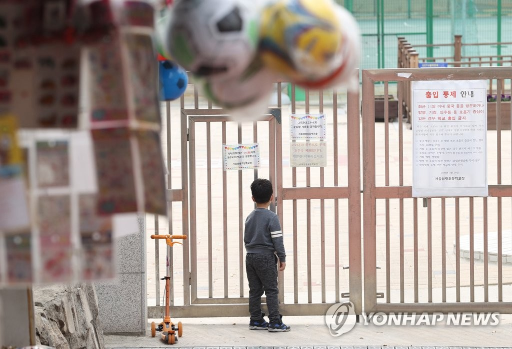 In this file photo from March 31, 2020, a boy looks through closed gates at an elementary school in the Yongsan district of central Seoul. (Yonhap)