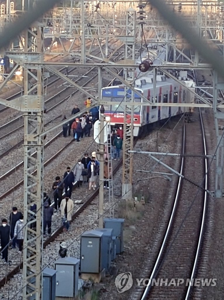 In this photo, provided by a reader, passengers walk along the railway after evacuating a subway train that derailed near Yeongdeungpo Station in southwestern Seoul on April 14, 2020. (PHOTO NOT FOR SALE) (Yonhap)