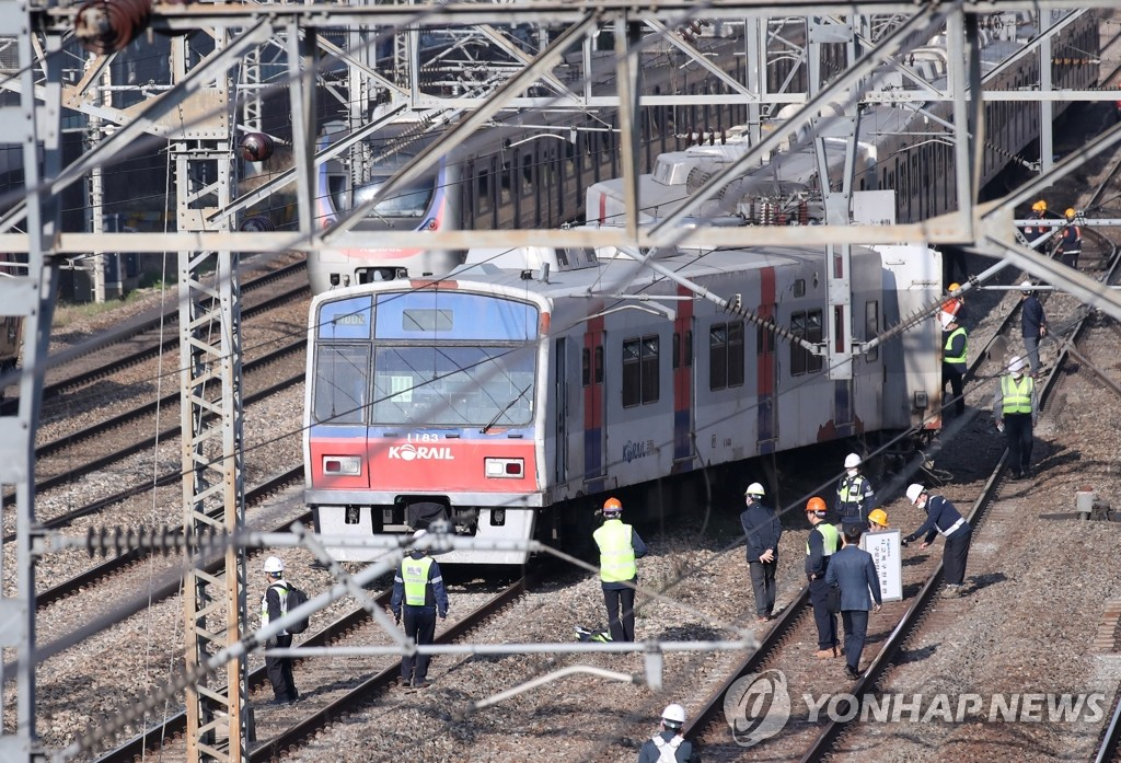Railway officials examine a derailed subway train near Yeongdeungpo Station in southwestern Seoul on April 14, 2020. (Yonhap)