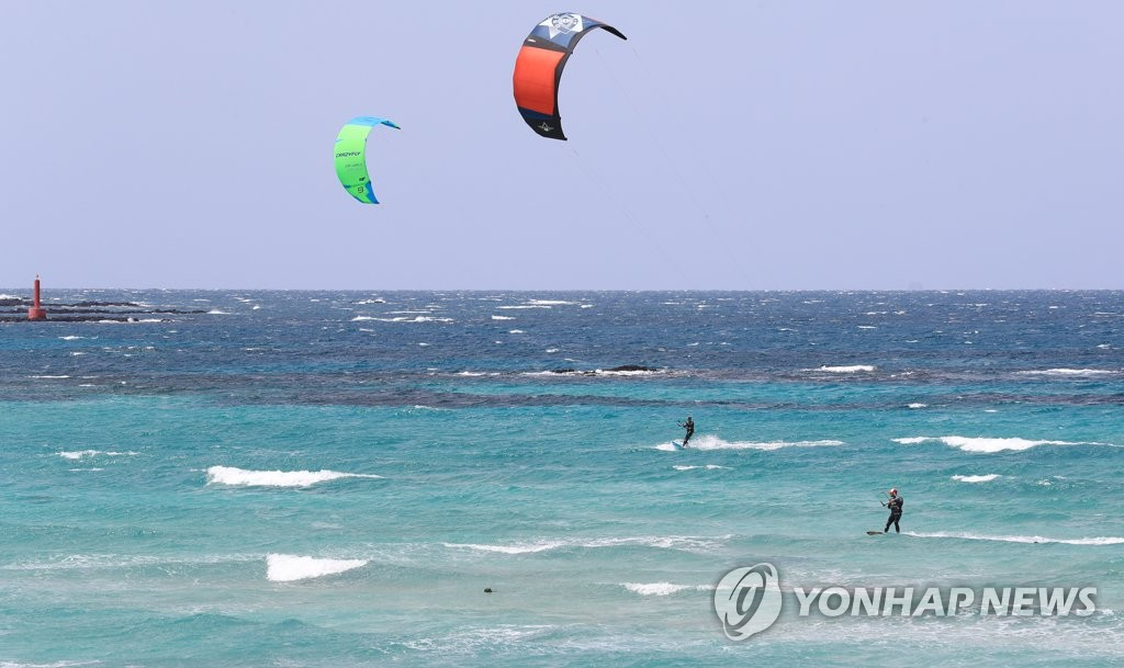 In this photo taken April 21, 2020, kitesurfers enjoy themselves at Hamdeok Beach, Jeju Island. (Yonhap)