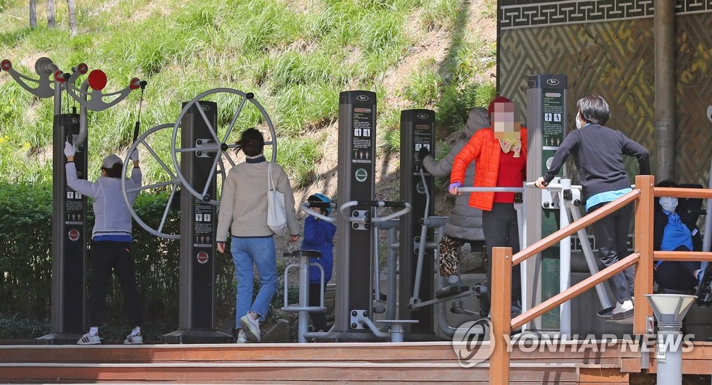 Citizens wearing face masks exercise using fitness equipment at a park in Seoul on April 24, 2020. (Yonhap)
