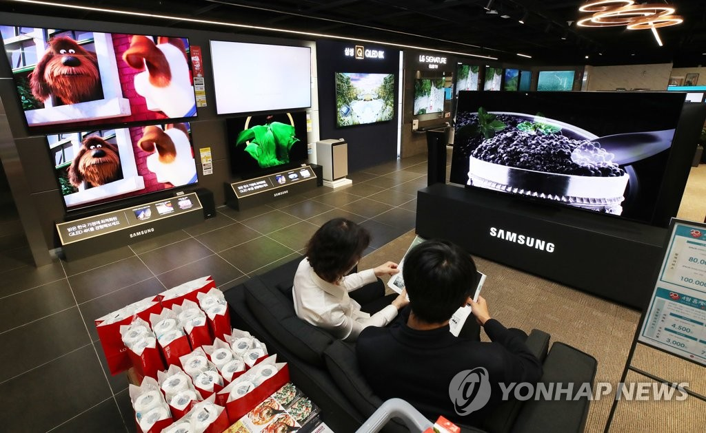 This file photo taken April 29, 2020, shows customers at a TV store in Seoul. (Yonhap)