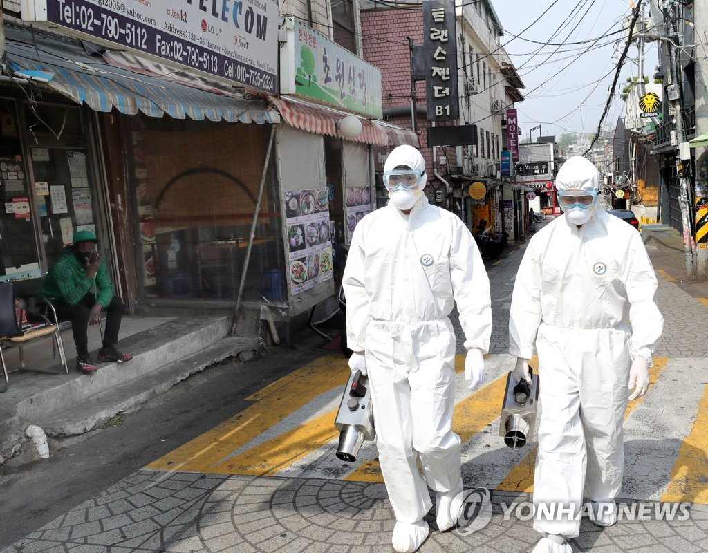 Quarantine workers carry out a disinfection operation in Seoul's popular multicultural neighborhood of Itaewon on May 11, 2020. (Yonhap)