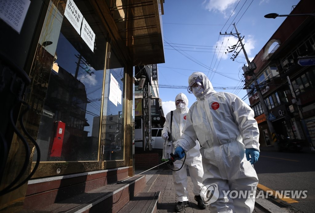 In the file photo taken May 12, 2020, volunteers spray disinfectant on a street in the international district of Itaewon in Seoul after a cluster of more than 100 COVID-19 infection cases have been linked to popular nightspots there. (Yonhap)