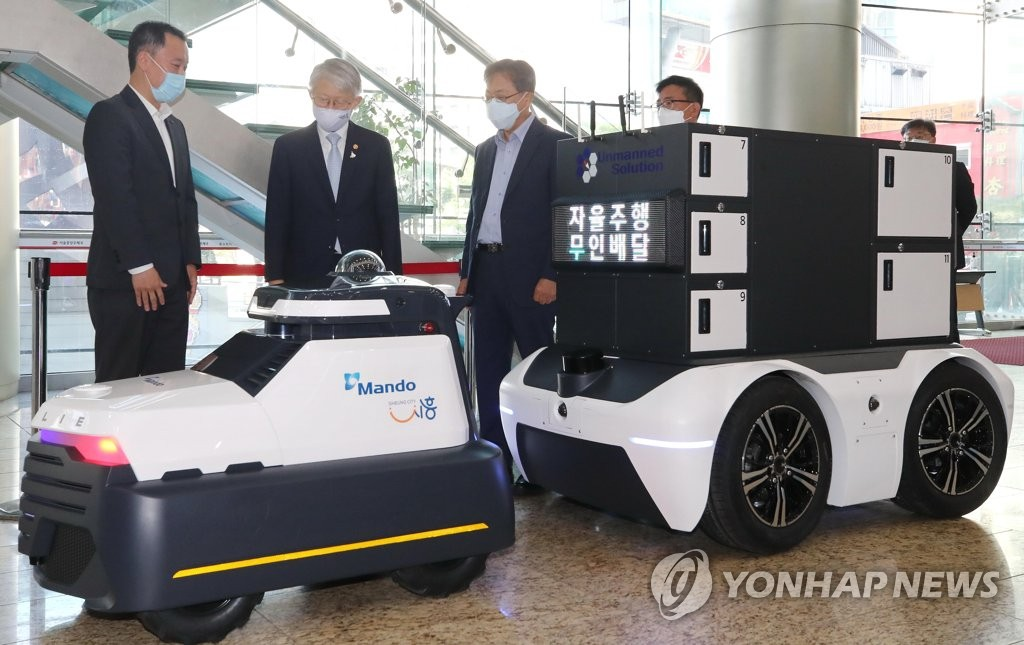 Minister of Science and ICT Choi Ki-young (2nd from L) looks over autonomous delivery and park patrol robots on display in downtown Seoul on May 13, 2020.