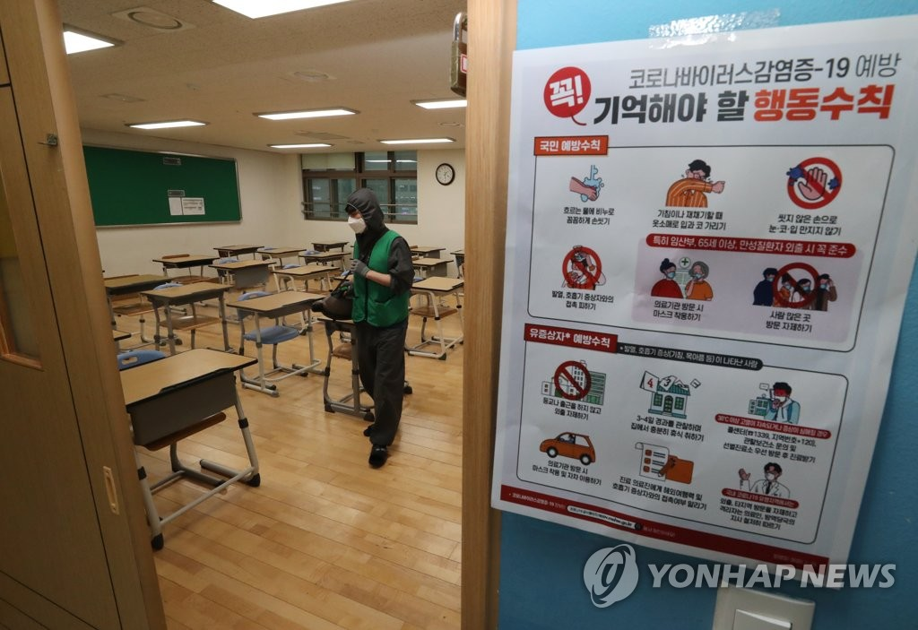 A quarantine official disinfects a classroom in a high school in the administrative city of Sejong on May 18, 2020. (Yonhap)