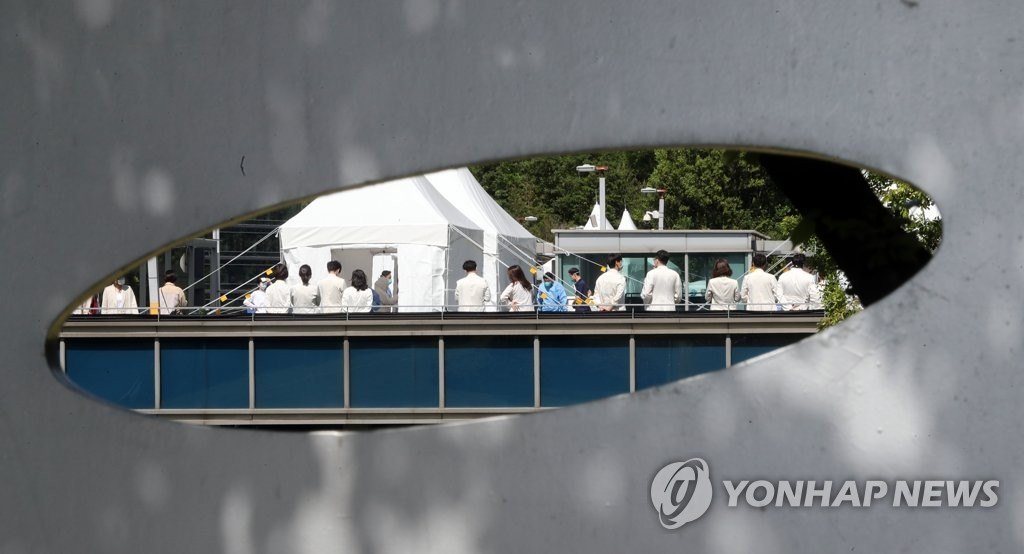 Hospital staff wait to be checked for coronavirus at an screening center set up at Samsung Medical Center's outdoor parking lot in the southern Seoul ward of Gangnam on May 19, 2020. (Yonhap)