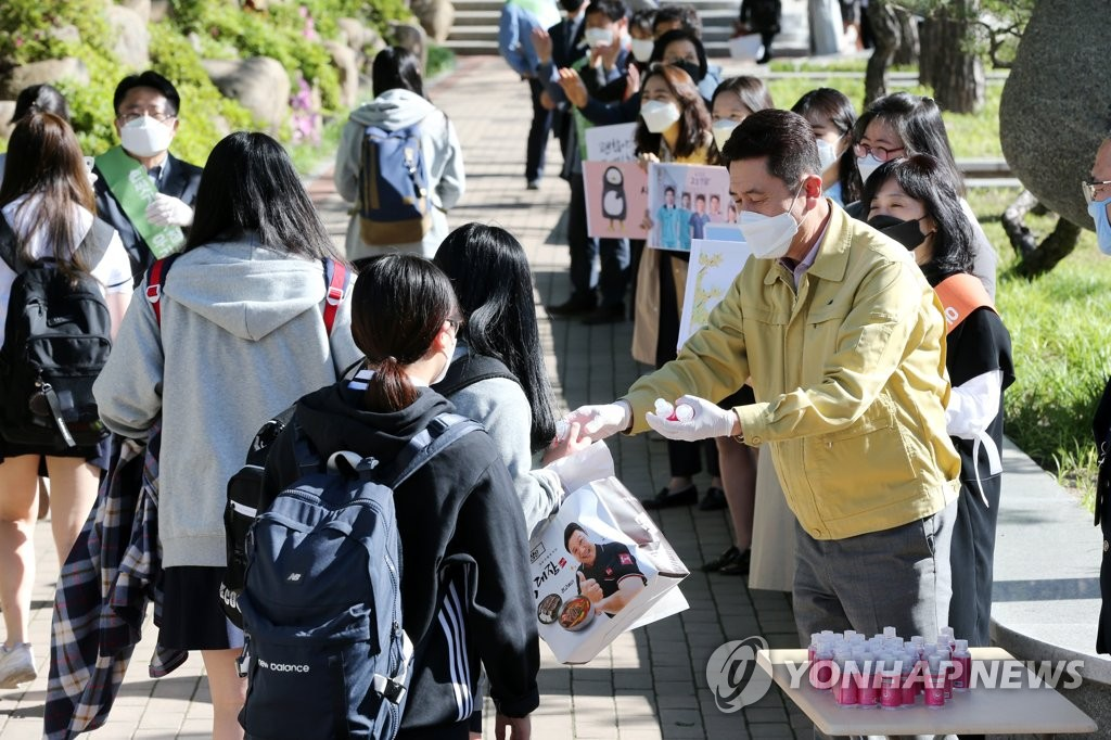 A teacher hands out bottles of hand sanitizer to students at a high school in the southeastern city of Pohang on May 20, 2020. (Yonhap)