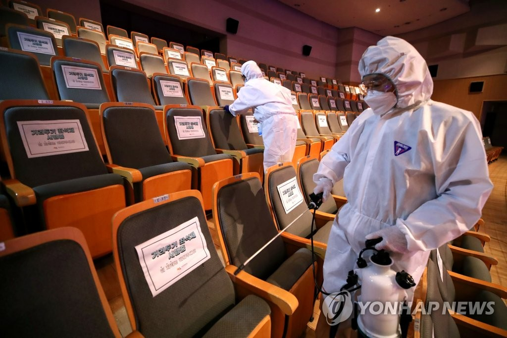 This May 21, 2020 file photo shows health workers disinfecting seats at a concert hall in the western Seoul ward of Mapo. (Yonhap)