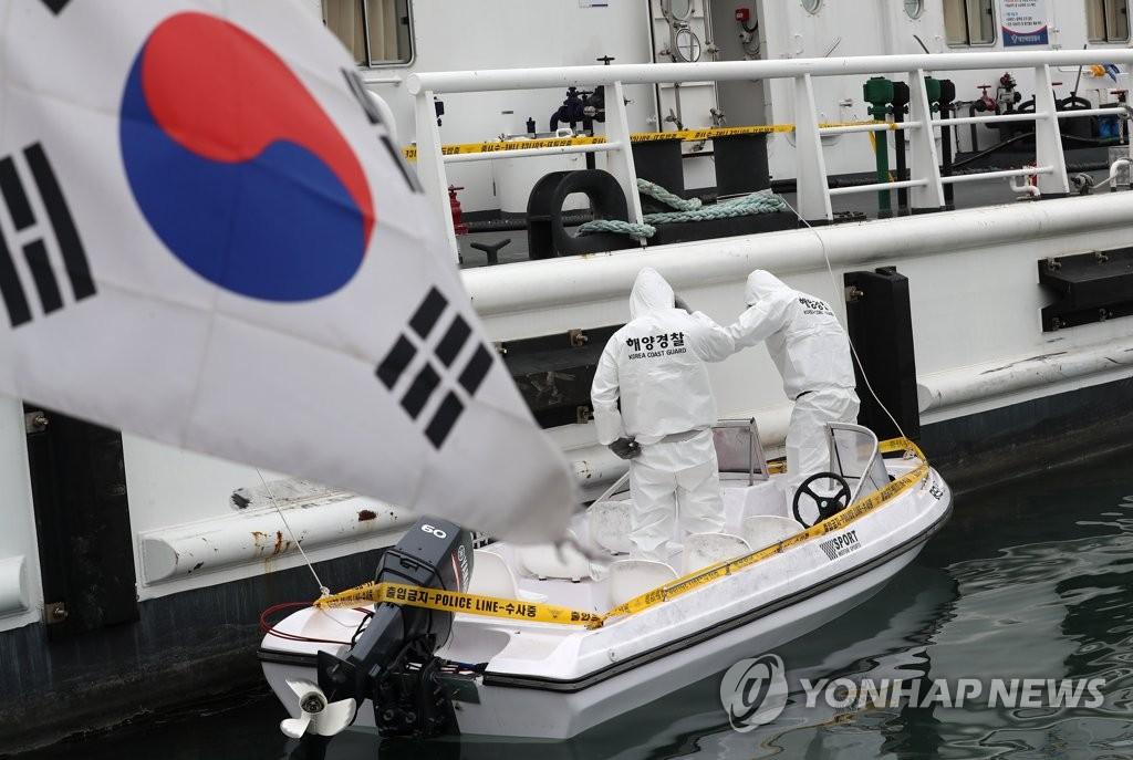 This file photo shows coast Guard officials inspecting a 1.5-ton boat found abandoned in the western coastal town of Taean, South Chungcheong Province. It was apparently used by a group of apparent Chinese nationals who entered South Korea illegally. (Yonhap)