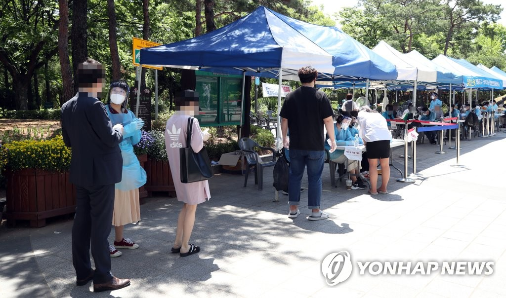 People line up to get tested for the new coronavirus at a walk-thru testing site at a park in Seoul on June 1, 2020. (Yonhap)