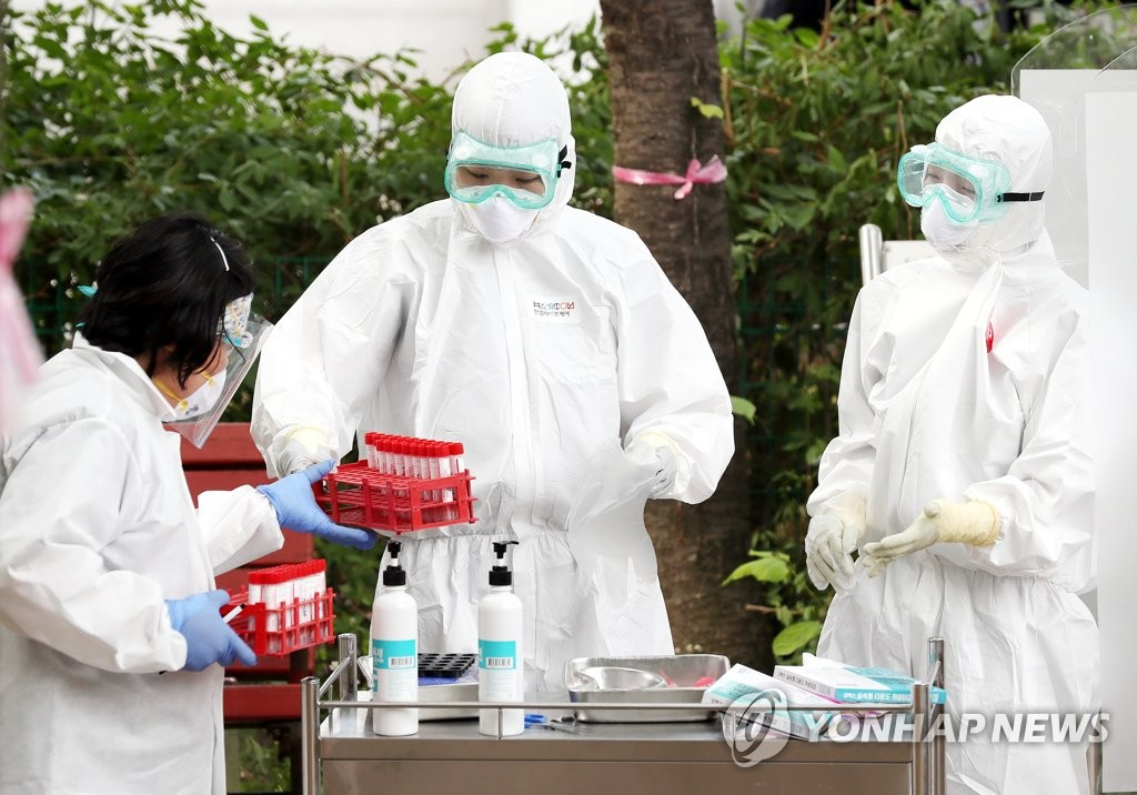 Health workers prepare to conduct coronavirus tests at a screening site in Bucheon, just west of Seoul, on June 17, 2020.