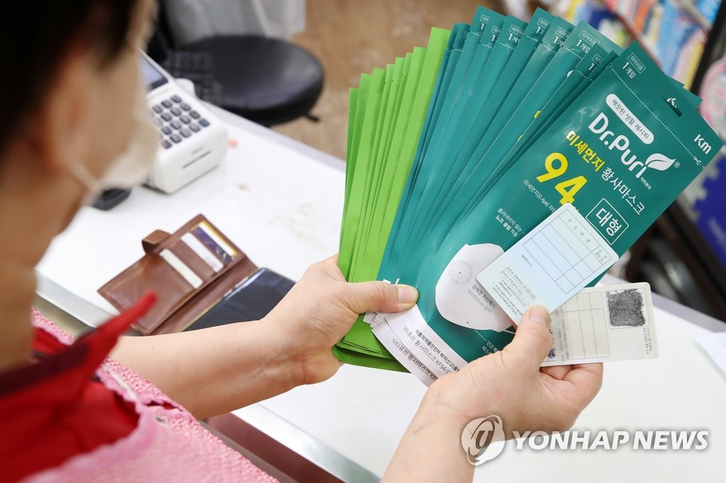 A citizen buys facial masks at a pharmacy in Jongno, central Seoul, on June 18, 2020, as South Korea began to allow people to purchase up to 10 masks per week under a state-led rationing program. (Yonhap)