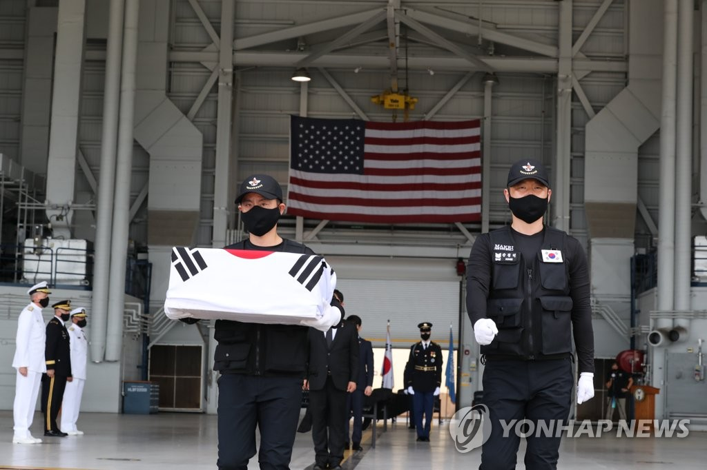 Members of South Korea's Agency for KIA Recovery & Identification carry flag-draped caskets of war dead remains at Joint Base Pearl Harbor-Hickam in Hawaii on June 23, 2020 in this photo provided by the Defense Media Agency provided this photo. (PHOTO NOT FOR SALE) (Yonhap)