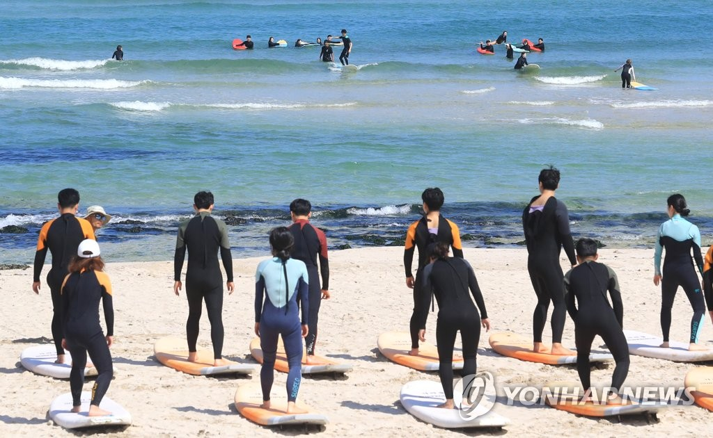 In this photo taken on June 26, 2020, surfers take a lesson at Gwakji Beach on Jeju Island. (Yonhap)