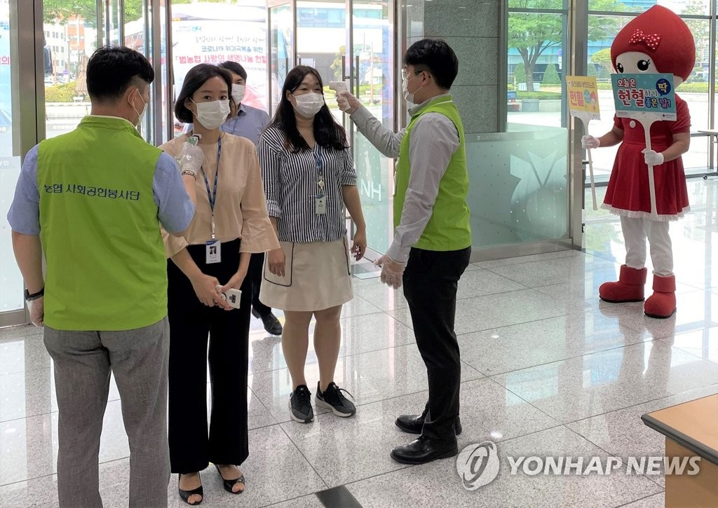 Workers at the National Agricultural Cooperative Federation (NACF) have their temperature checked at the headquarters in central Seoul on June 29, 2020, before they donate blood in this photo provided by the NACF. (PHOTO NOT FOR SALE) (Yonhap)